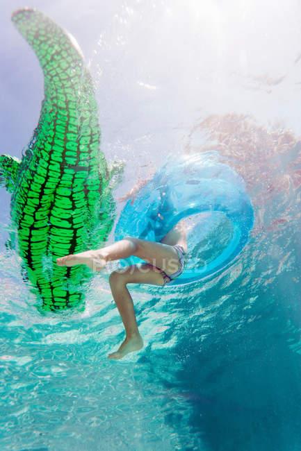 Criança brincando com brinquedos na piscina de flutuação — Fotografia de Stock