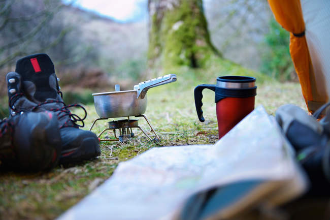 Pair of hiking boots, cooking stove and hot mug — Stock Photo