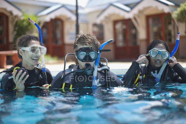 Three young adult scuba divers training in swimming pool — Stock Photo