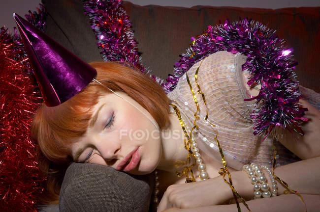 Жінка з партії капелюх спала на дивані — стокове фото