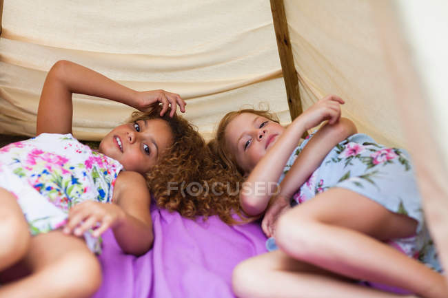 Girls laying together in tent outdoors — Stock Photo