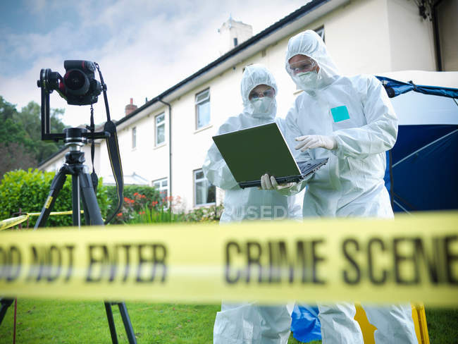 Forensic scientists using laptop behind police tape at crime scene — Stock Photo