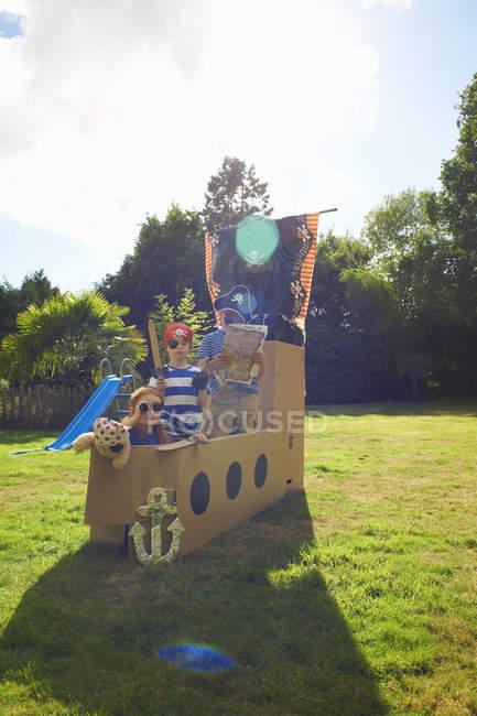 Двоє братів і сестри грають у саду з домашнім піратським кораблем — стокове фото