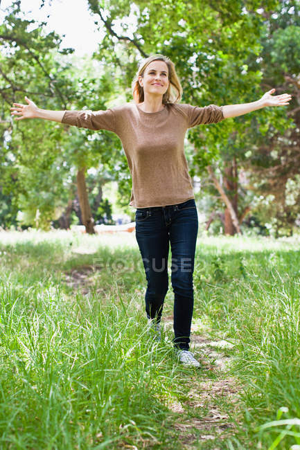 Женщина с поднятыми руками гуляет в парке — стоковое фото