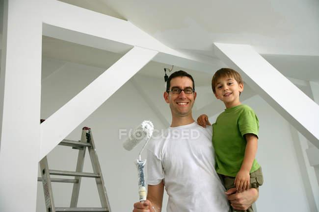 Vater und Sohn streichen neues Haus — Stockfoto