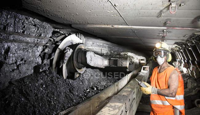 Exploitant abattant du charbon au front de taille dans une mine profonde — Photo de stock