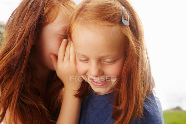 Girls whispering to each other outdoors — Stock Photo