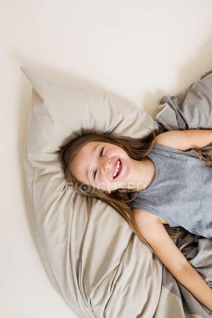 Vista aérea de la chica sonriente acostada en la cama - foto de stock