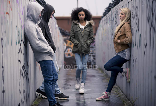 Teenagers standing against wall with graffiti — Stock Photo