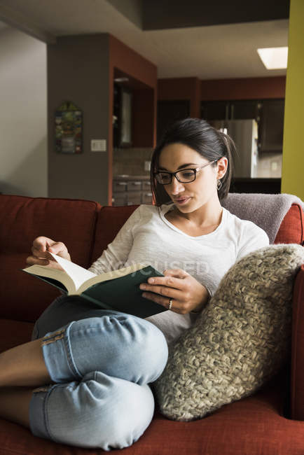 Woman reading book on sofa at home — Stock Photo