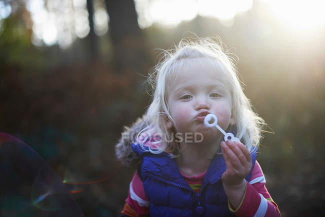 Menina da criança soprando bolhas no parque outonal em backlit — Fotografia de Stock