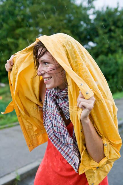 Улыбающаяся женщина, закрывающая волосы под дождем — стоковое фото
