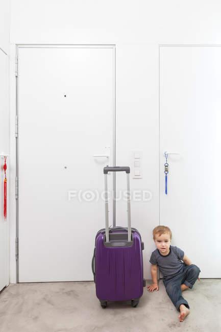 Хлопчик шляхом прокатки багажу в коридорі — стокове фото