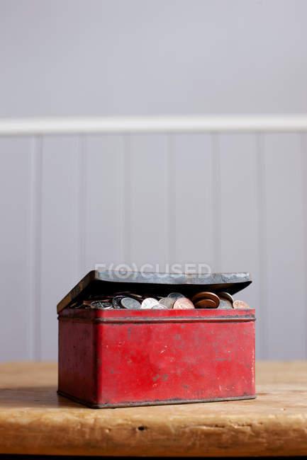 Античний олово повний гроші на столі — стокове фото