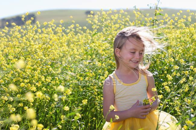 Усміхнена дівчина грає в полі квітів — стокове фото