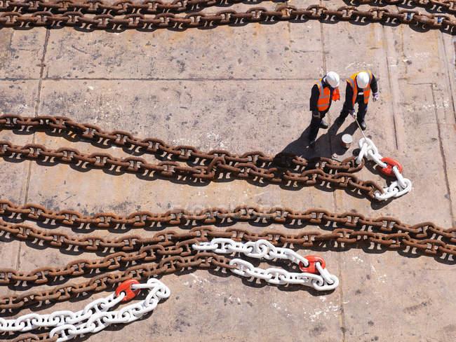 Рабочие с якорной цепью в сухом доке — стоковое фото