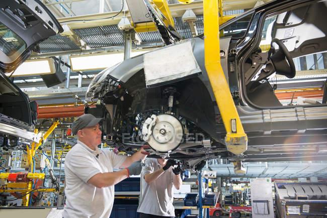 Operatori del montaggio di automobili che montano assi alle automobili sulla linea di produzione in fabbrica di automobili — Foto stock