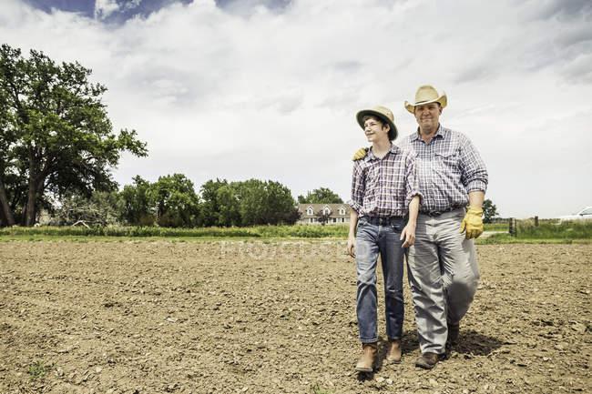 Agriculteur et petit-fils adolescent marchant sur champ labouré — Photo de stock