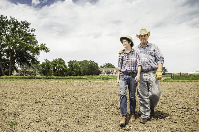 Farmer and teenage grandson walking over ploughed field — Stock Photo