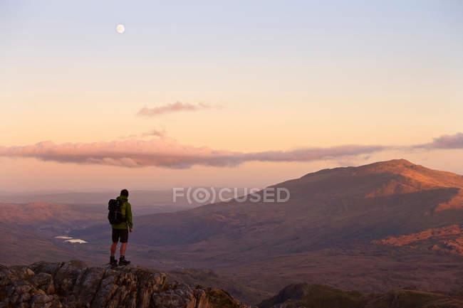 Людина стоїть на вершині гори. — стокове фото