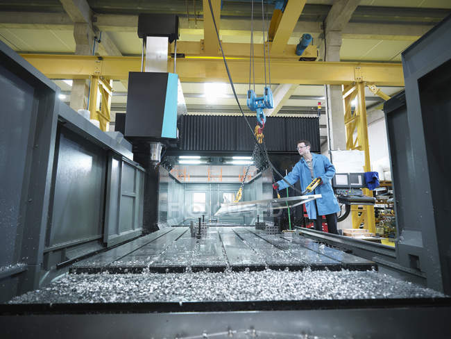 Worker in large CNC machine in plastics factory — Stock Photo