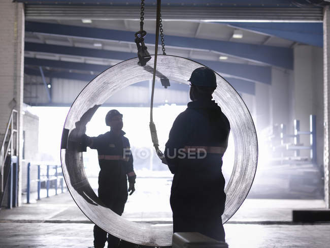 Engenheiros usando guindaste para levantar grande tubo de aço na fábrica de engenharia — Fotografia de Stock