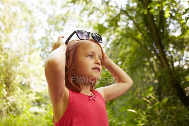 Усміхнена дівчина грає з сонцезахисних окулярів — стокове фото