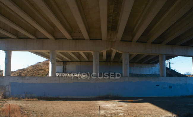 Bottom view of overpass concrete structure with pillars — Stock Photo
