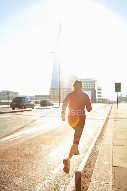 Femme courant dans la rue de la ville — Photo de stock