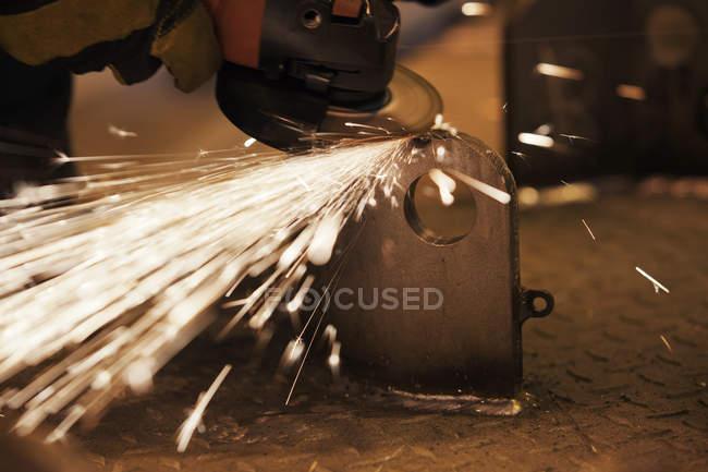 Funkenflug von Arbeiter mit Mühle in Fabrik — Stockfoto