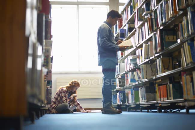 Jeunes étudiantes et étudiants masculins et féminins travaillant à la bibliothèque — Photo de stock
