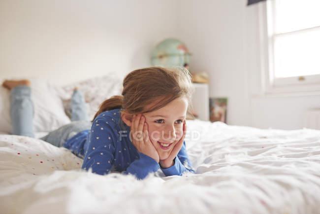 Menina deitada na cama coberta de penas brancas — Fotografia de Stock