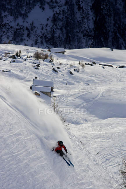 Skier turning down a slope in winter — стоковое фото