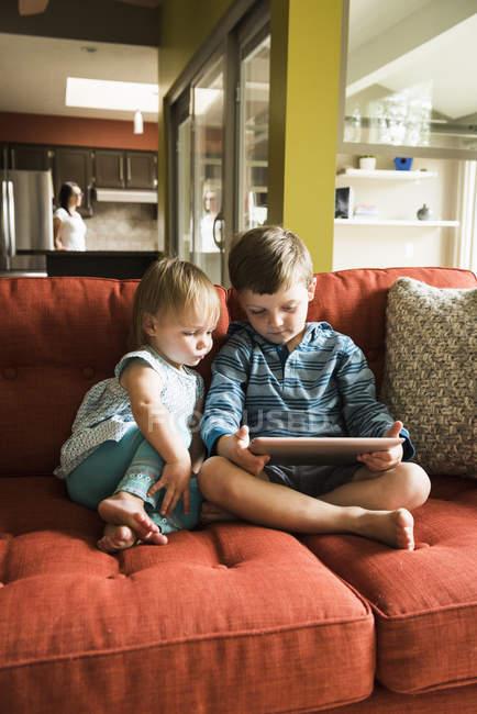 Geschwister nutzen digitales Tablet auf dem heimischen Sofa — Stockfoto