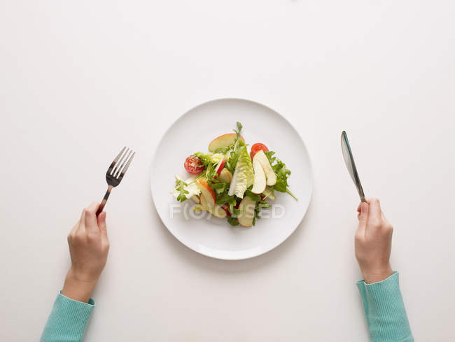 Hands holding fork and knife by salad — Stock Photo