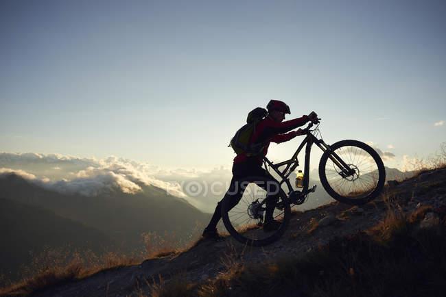 Mountainbiker drängen Fahrrad bergauf, Wallis, Schweiz — Stockfoto