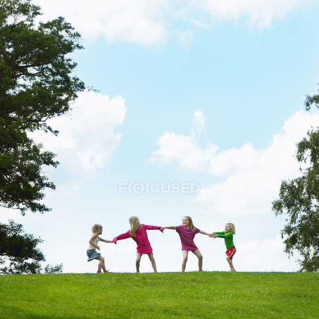 Girls playing tug-of-war in field against blue sky — Stock Photo