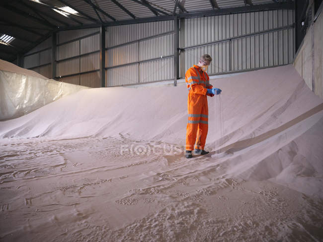 Worker in reflective clothing inspecting zircon sand — Stock Photo