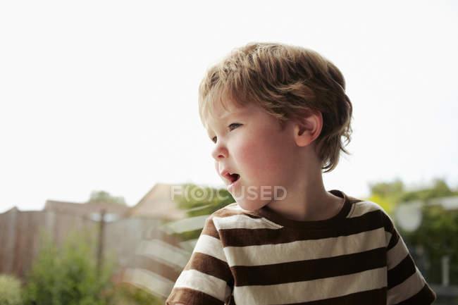 Мальчик сидит у окна и смотрит в сторону — стоковое фото