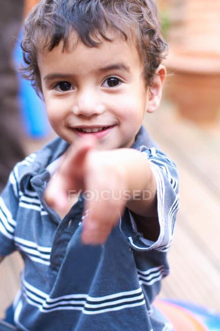 Улыбающийся мальчик указывает вперед — стоковое фото