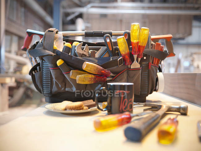 Tool kit with cup and biscuits on plate — Stock Photo