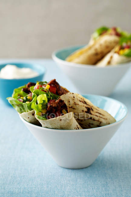 Tortilla wraps in bowls on blue table — Stock Photo