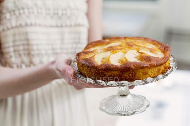 Vista cortada de mulher segurando bolo em cakestand de vidro — Fotografia de Stock