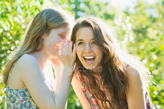 Teenage girls whispering outdoors — Stock Photo