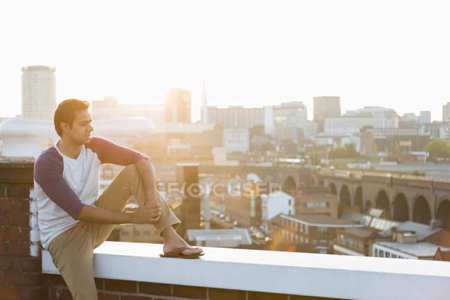 Man sitting on wall on rooftop, Birmingham, England, UK — Stock Photo