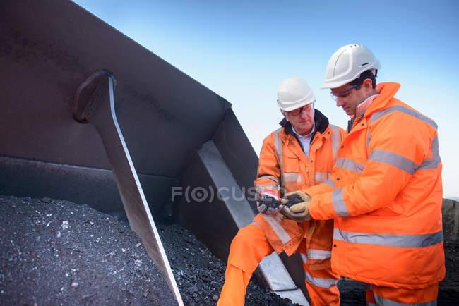 Trabajadores que inspeccionan carbón en minas de carbón de superficie - foto de stock