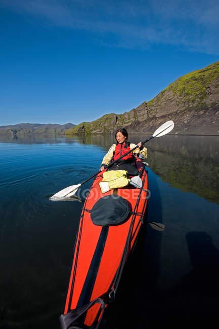 Woman rowing kayak in still lake — Stock Photo