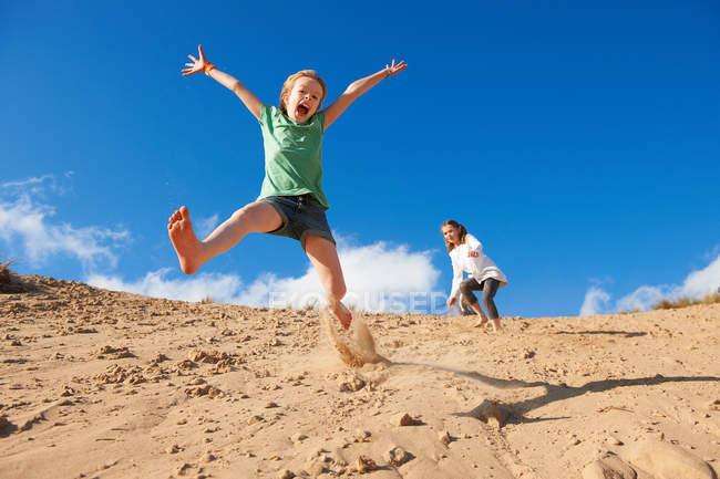 Due ragazze che saltano sulle dune della spiaggia — Foto stock
