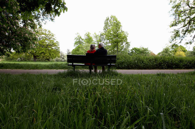 Couple plus âgé assis sur le banc du parc — Photo de stock