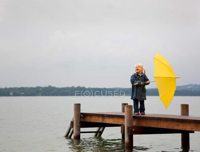 Fille tenant parapluie jaune sur le quai — Photo de stock